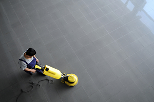 A technician waxes and buffs an office building floor